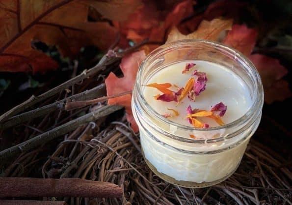 A jar of calendula rose lotion with petals.