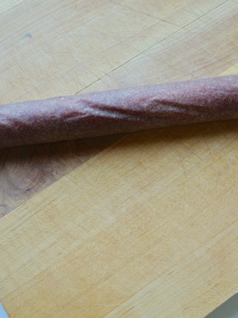 Yellow plum fruit leather rolled up into a spiral tube for cutting.