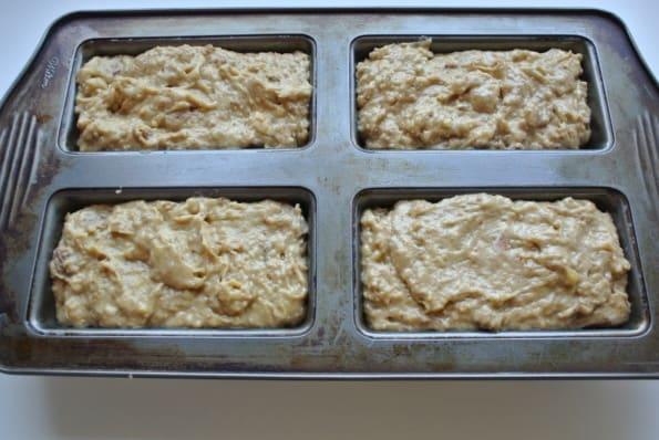 Banana date bread batter in four mini bread pans.
