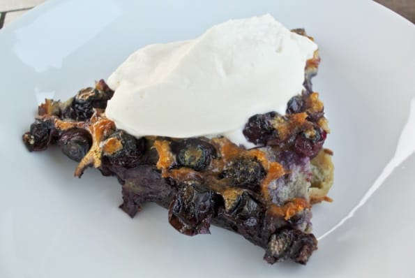 A slice of warm blueberry clafoutis with whipped cream.