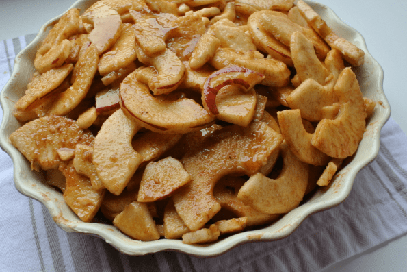 Thinly sliced apples are coated in maple syrup and spices before baking.