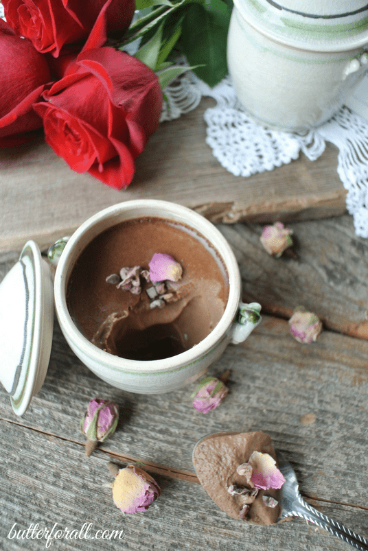 A petit chocolate rose pot de crème topped with rose petals on a wood table with red roses.