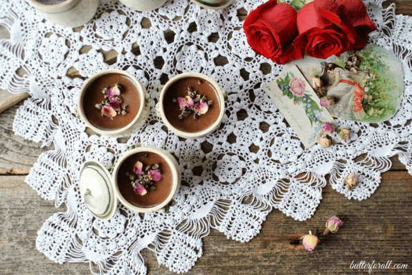 Three petit chocolate rose pots de crème topped with rose petals on a lace tablecloth with red roses.