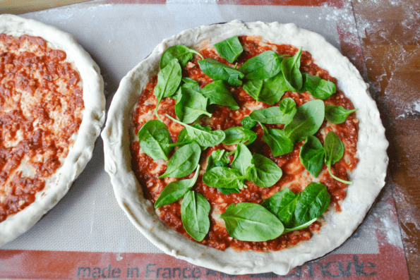 Sourdough pizza crusts with sauce and spinach.
