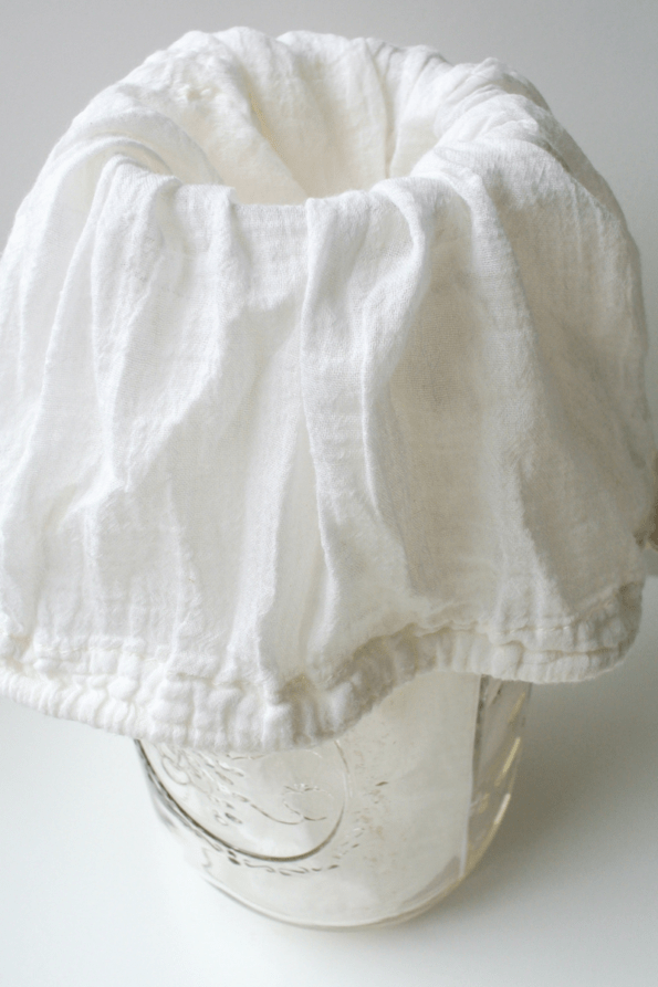 A jar of clabber with a cotton bag on top for straining.