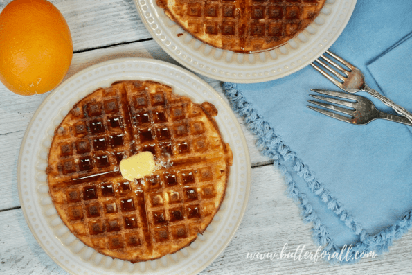 A sourdough waffle on a plate covered in maple syrup.