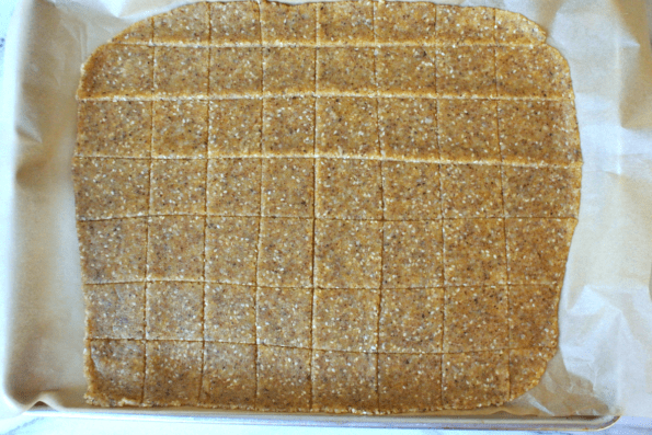 Sesame, cheese, and nut cracker dough rolled out and scored into squares.