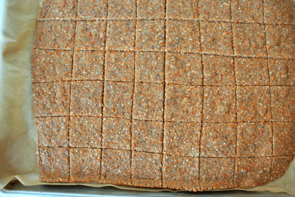 A close-up of sesame, cheese, and nut cracker dough rolled out and scored into squares.
