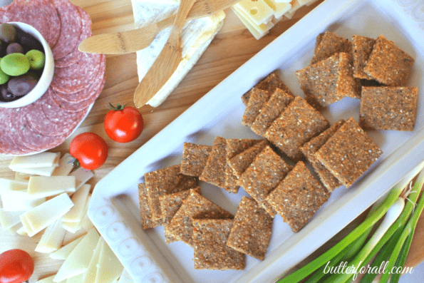 A plate of low-carb sesame, cheese, and nut crackers with cheese and sliced meat.