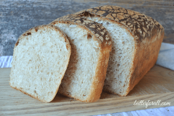 A loaf of butter top sourdough sliced to show the crumb.