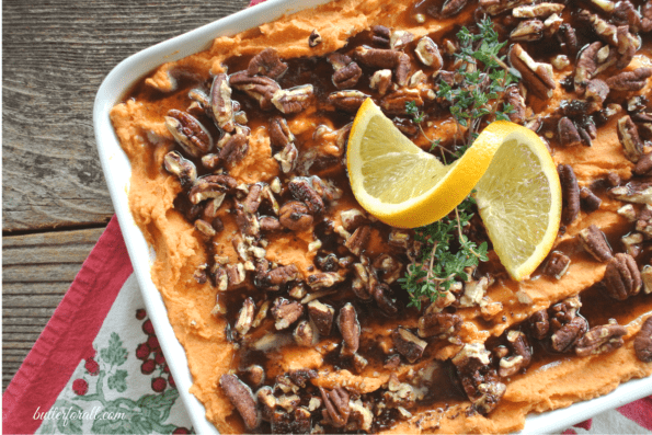 A large casserole dish filled with rich and creamy sweet potato mash and topped with cinnamon maple pecans.