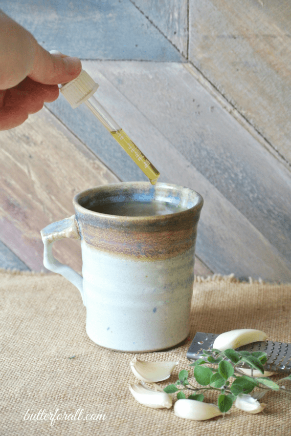 A mug of cold and flu buster with oregano oil being added.
