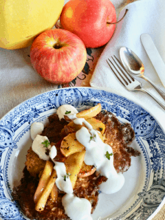 A pretty plate with crispy latkes topped with sautéed apples and sour cream.