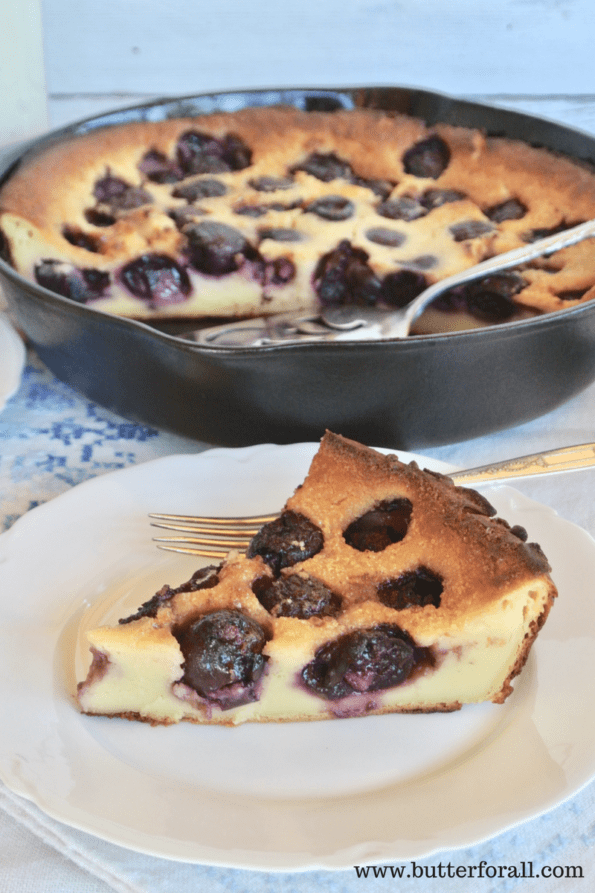 A pan and a slice of sourdough clafoutis fresh out of the oven and bursting with black cherries.