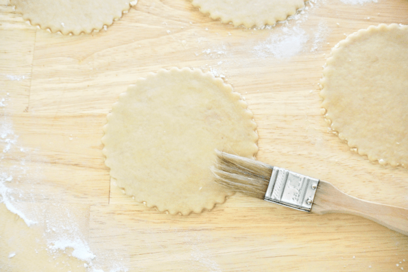 Each mini pie crust is brushed with water to help them seal.