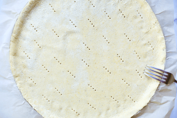 Fitting the sourdough and masa harina cornmeal crust into a pizza pan and docking the crust before baking.