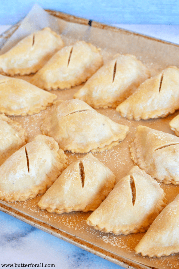The pies are placed on a parchment lined baking sheet.