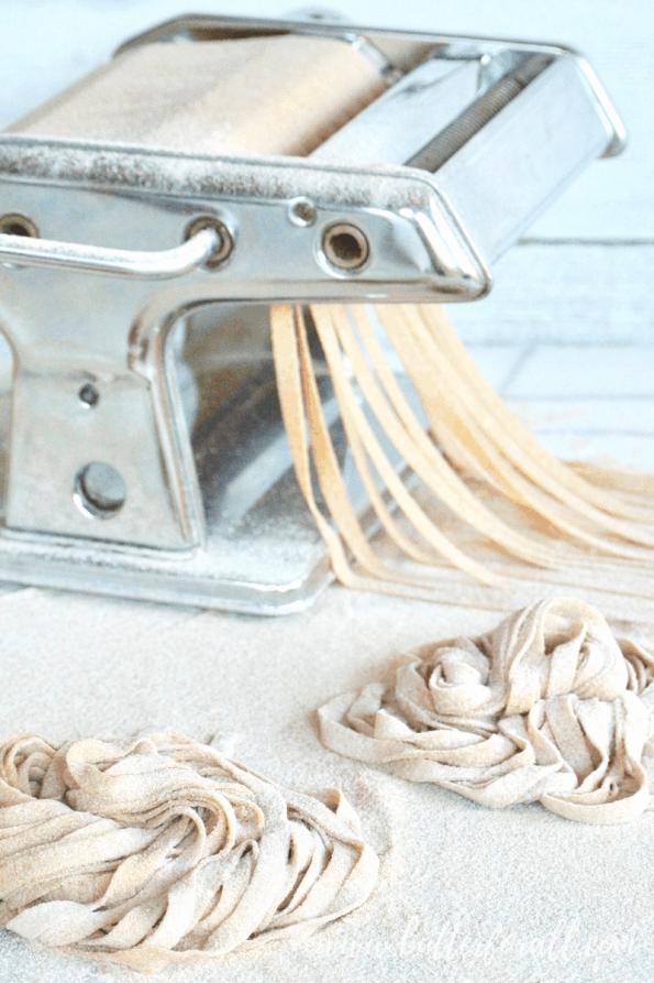 Cutting sourdough noodles in a pasta machine.