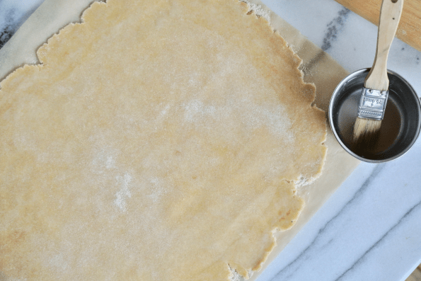 Bush the edges of the Sourdough pastry with water.