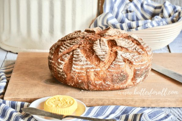 A tall boule of fresh whole grain sourdough bread perfect for eating with raw butter.