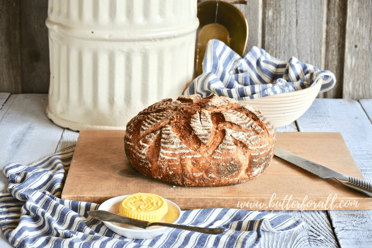 A beautiful loaf of fresh whole grain sourdough sits atop a cutting board just waiting to be cut.