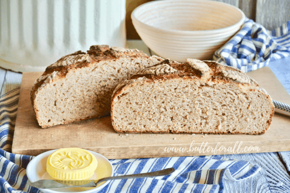 A soft and chewy loaf of sourdough bread cut in half to reveal the sweet whole grain crumb.