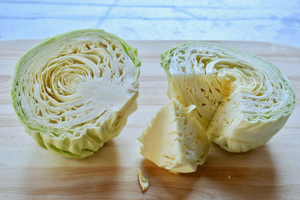 The Cabbage head is cut in half and cored.