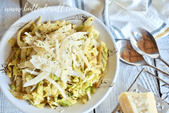 A bowl of keto-friendly cabbage noodles topped with fresh shaved Parmesan cheese.