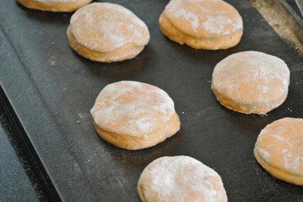 Cooking the English muffins on a cast iron griddle.