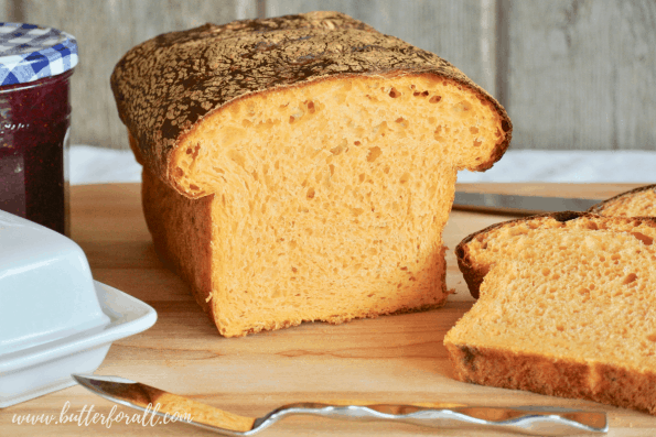 A loaf of Sweet Potato Sourdough bread is perfectly soft with a gorgeous orange color.