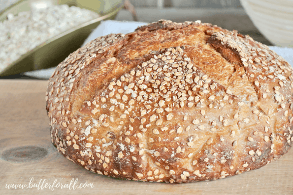 A big loaf of sweet and soft honey oat sourdough bread perfectly browned from the oven.