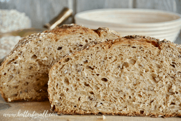 Cutting into the crumb of this honey oat sourdough reveals a light and airy texture.