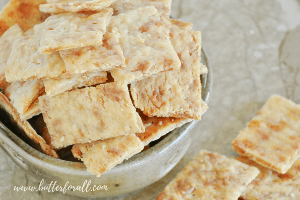 A bowl of the butteriest, flakiest, crunchiest sourdough cheese crackers made with fully fermented sourdough starter, real butter and real cheese. #starter #sourdough #wildyeast #fermented #realfood #wisetraditions #crackers #cheesecrackers #healthysnacks #easy #crunchysnacks