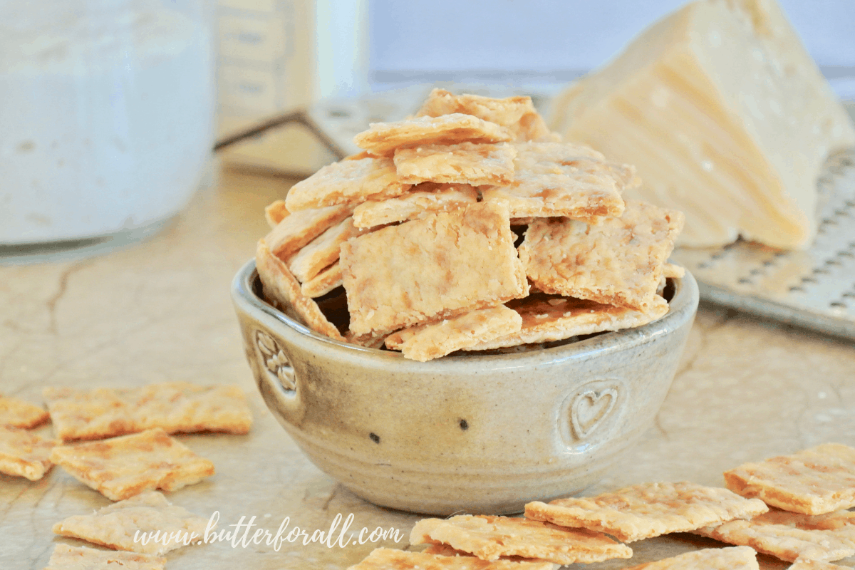 A bowl of these super crispy and crunchy Buttery Parmesan Sourdough Discard Crackers makes an excellent homemade snack. #starter #sourdough #wildyeast #fermented #realfood #wisetraditions #crackers #cheesecrackers #healthysnacks #easy #crunchysnacks