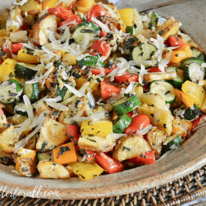 A perfect platter of Sheet-Pan Roasted Vegetables garnished with fresh Parmesan cheese and basil makes an easy and impressive side dish busting with color and flavor! #realfood #onepan #easy #summer #potluck #potatoes #squash #peppers #herbs #parmesan #basil #sidedish #entertaining