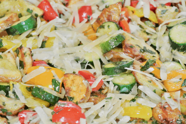 Add the Parmesan cheese and basil to the freshly roasted vegetables as soon as they come out of the oven.