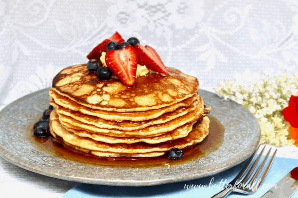 A plate of sourdough pancakes with syrup and fresh berries.