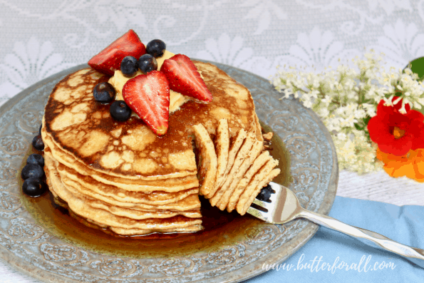 A stack of sourdough pancakes with syrup and fresh berries.