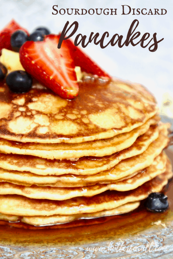 A stack of sourdough pancakes with syrup and fresh berries with text overlay.