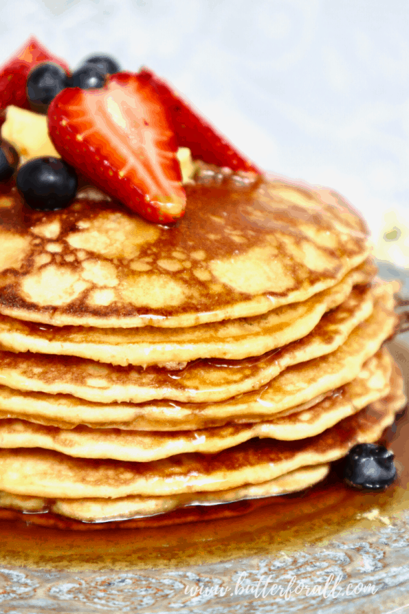 A close-up of a stack of sourdough pancakes with syrup and fresh berries.