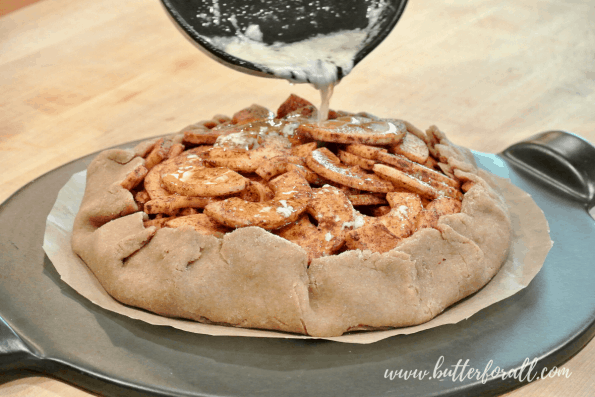 Pouring melted butter over the Apple Galette.