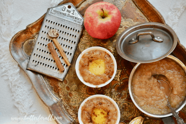 Bowls of hot buttered apple sauce on a tray with ingredients.