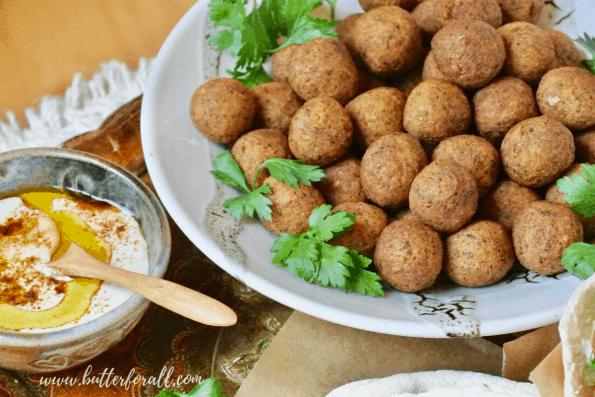 A bowl of falafel balls with tahini.