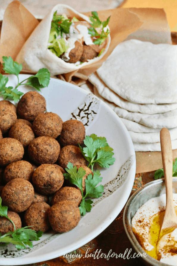 A bowl of falafel balls with pita and tahini.