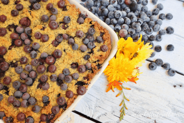 Image showing a pan of blueberry cornbread as a cake topped with fresh blueberries.
