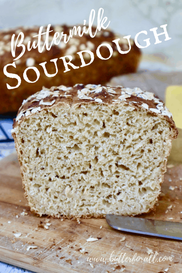 Pinterest image of a sliced loaf of Buttermilk Sourdough showing the open and textured inner crumb.
