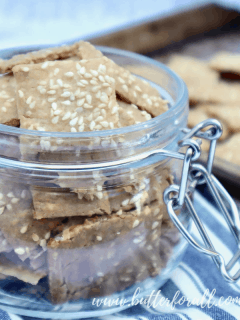 A Jar full of toasty brown sesame crackers with a baking sheet of crackers in the background.