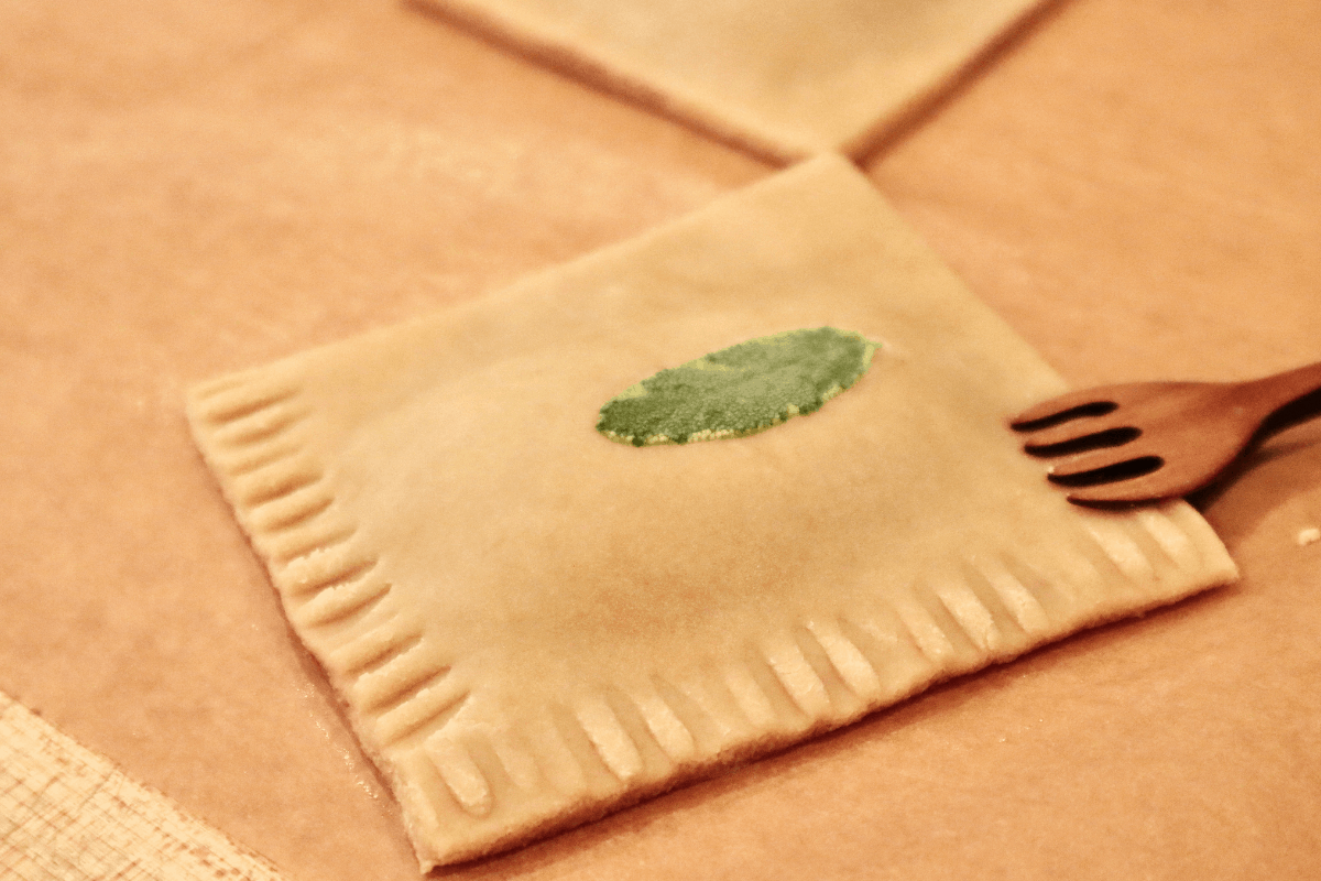 A raw pastry square being crimped around each edge with a fork.