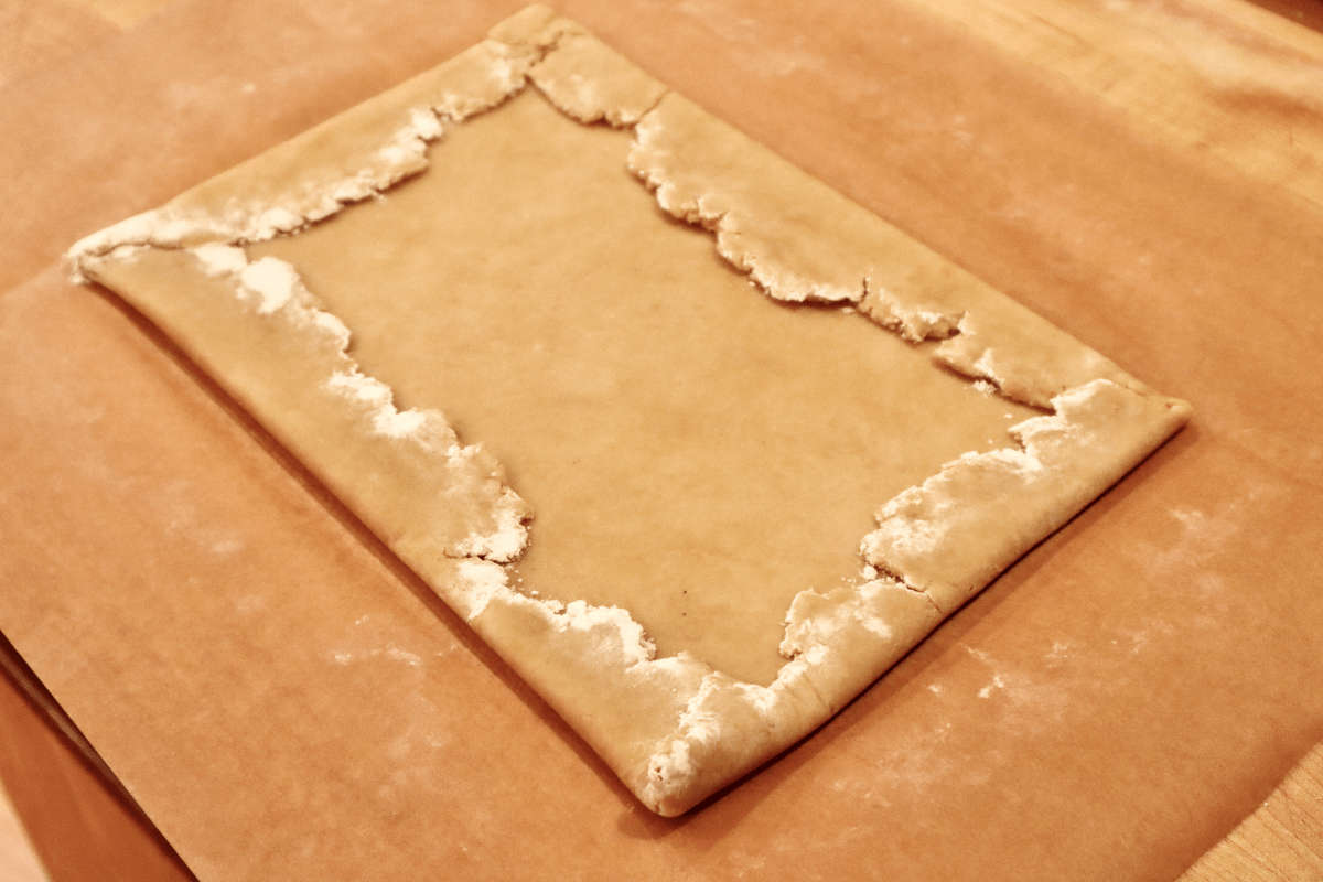 The jagged edges of the dough are folded over to make a tight rectangle.