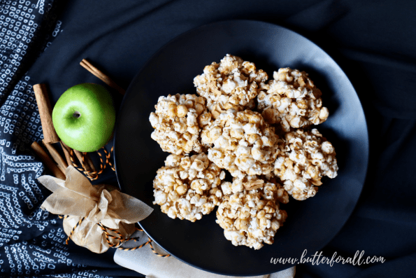 Plate of seven Cinnamon Apple Honey-Butter Caramel Popcorn Balls with festive decorations.